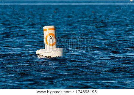 A 5 mph speed limit buoy in a harbor.
