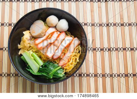 Egg noodle soup with red roast pork on wooden background.