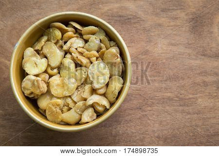 Salted broad beans in bowl on wooden background.