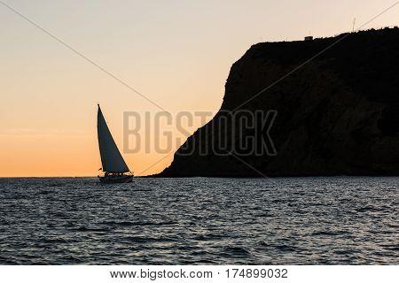 Sailboat near the Point Loma peninsula at sunset in San Diego, California.