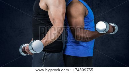 Mid section of healthy men working out with dumb bells against black background