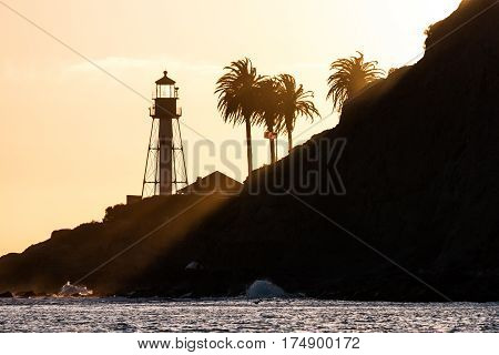 Sun rays shining on the new Point Loma lighthouse at sunset in San Diego, California.