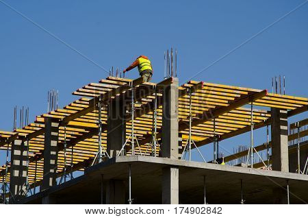Construction workers installing mounting horizontal formwork on the building construction site.