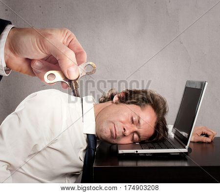 businessman with a key winder on his back sleeping on laptop