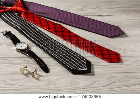 Black red and violet silk neckties watch with a leather strap cufflinks on a gray wooden background