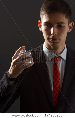 Young man in black suit and red necktie holding man perfume in his hand