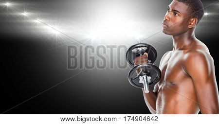 Healthy man working out with dumb bells against black illuminated background