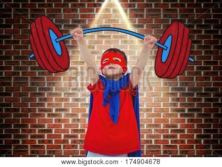 Boy in superhero costume holding a dumb bell against brick wall background