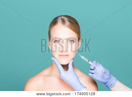 Young and beautiful woman having skin injections over teal background. Plastic surgery concept.