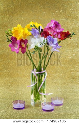 Colorful of freesia in vase and candles on a yellow background