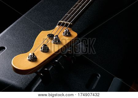 Electric Bass guitar headstock on black leather hard case isolated on black background
