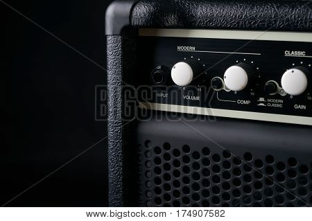 Electric bass Guitar black leather Amplifier on black Background.