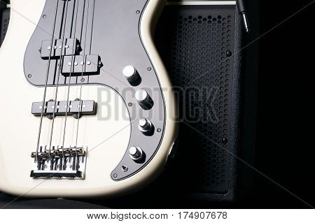 Black and white electric bass guitar with jack cable and classic amplifier on a dark background.Close up.