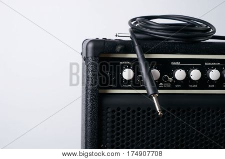 Close up of Black guitar amplifier with jack cable on white background.