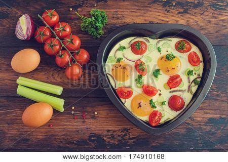 Romantic breakfast for Valentine day or anniversary fried eggs with tomatoes celery onion and parsley in heart shaped baking dish. Rustic wooden table fresh vegetables ingredients for cooking. Top view.