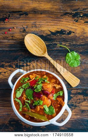 Turkey chili stewed with beans tomatoes bell pepper onion garlic thyme cinnamon chocolate and fresh cilantro. White pot on wooden table top view.