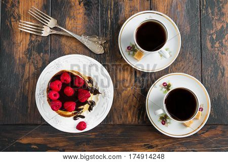 Stack of homemade pancakes with raspberries and chocolate vintage white plate and forks and cups with black coffee on wooden table. Top view.