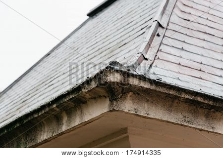 Detail of old building cornice against overcast sky