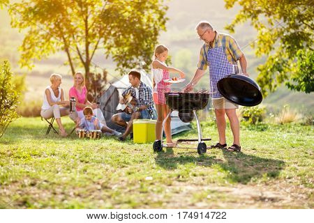Grandfather and granddaughter at barbecue grill with family having diner