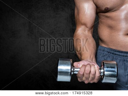 Mid-section of man performing dumbbell curl exercise against black background