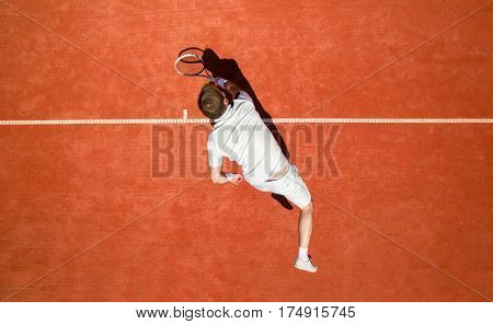 Top view of male tennis player hitting ball with racket