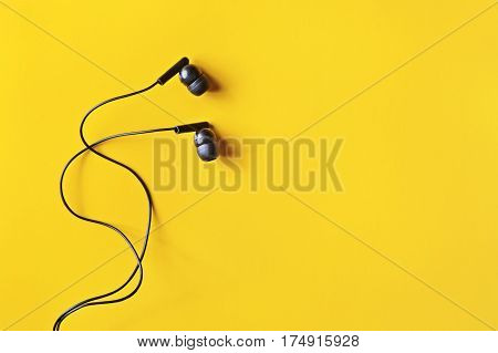 Flat lay concept: headphones on pastel backgrounds. Black headphones on a yellow background top view copyspace. Trendy colorful photo. Minimal style with colorful paper backdrop.