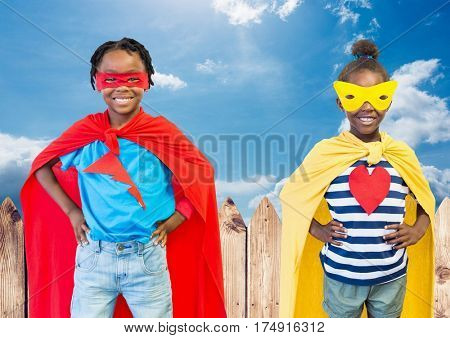 Digital composition of kids in superhero costume with hands on their waist standing against sky in background