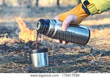 Man pours in a cup or mug hot coffee tea or mokka from a thermos bottle outdoor near the campfire in the forest closeup. People and healthy lifestyle concept. Theme adventure travel tourism and camping concept.