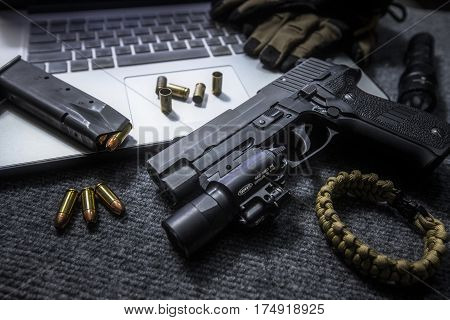 pistol and bullet on the table with labtop