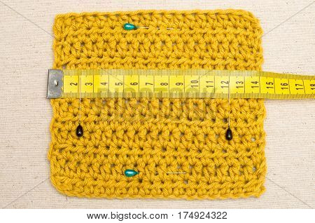 Tape Measure On Crocheted Fabric With Fastened Pins