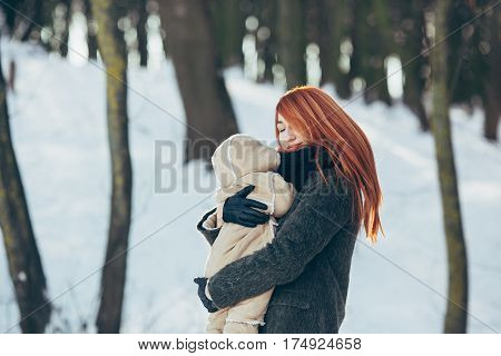 Mom and baby in the park in winter