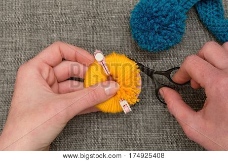 Hands Cutting Yellow Yarn Wrapped Around Pom-pom Maker