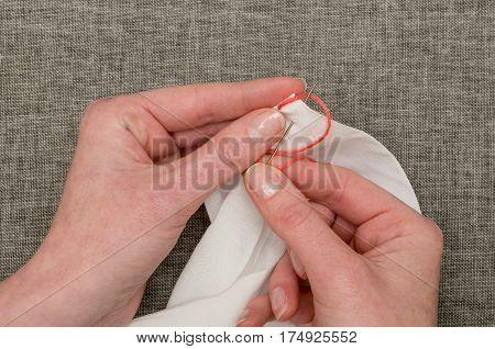 Hands Sewing Orange Yarn Through Shirt Sleeve