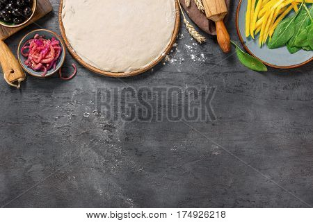 Various raw ingredients for cooking vegetarian pizza on the dark stone surface with copy space top view. Healthy food