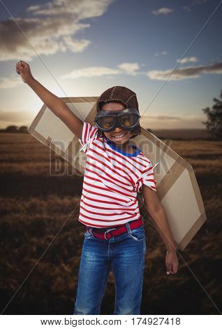 Composite image of smiling kid pretending to be a pilot in field