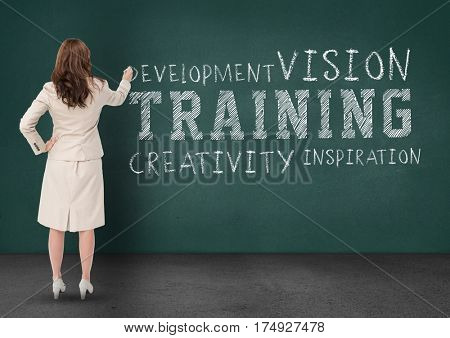 Digital composite of businesswoman writing business terms on chalkboard