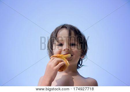 Cute Child,  Boy, Eating Croissant On The Beach
