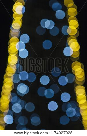 Blue and yellow glitter bokeh lights on a dark background. Useful as an unfocused background. Copy space area available
