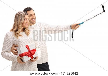 Young couple with a gift taking a selfie with a stick isolated on white background