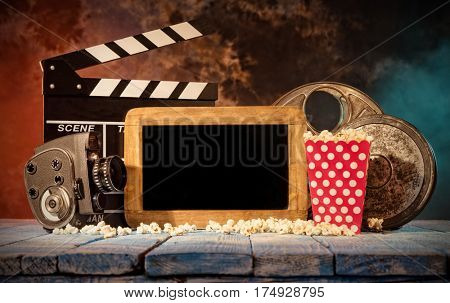 Retro film production accessories placed on wooden planks with blank blackboard for copyspace. Concept of film-making. Smoke effect on background