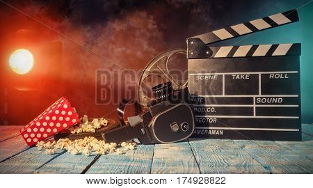 Retro film production accessories placed on wooden planks. Concept of film-making. Smoke effect with spot light on background