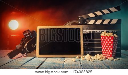 Retro film production accessories placed on wooden planks with blank blackboard for copyspace. Concept of film-making. Smoke effect with spot light on background