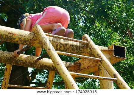 Cute little girl child climbing on a jungle gym at the playground outdoors.