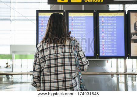 Back view of a young woman is checking her flight on a flight information board at the airport with a handbag hanged on her shoulder.