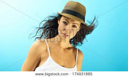 Portrait of attractive young woman at summertime over blue background.