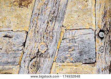 Detail of Old cracked oak timber in a timber-framed building. Oak wood structure with wattle and daub infill. Painted with yellow whitewash