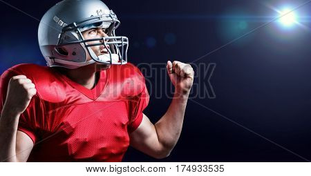 Digitally generated image of american football player cheering with clenched fist against blue background