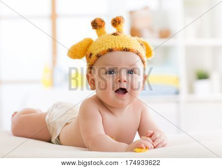 Baby boy in funny giraffe hat lying on his belly in nursery