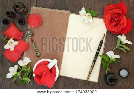 Rose and orange blossom flowers with essential oil glass bottles, mortar with pestle and hemp notebook, old pen and ink, on oak background.
