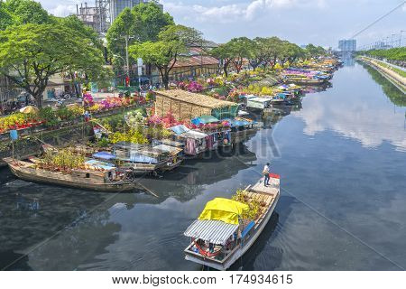 Ho Chi Minh City, Vietnam - January 26th, 2017: Boating along canal with apricot carry flowers, confetti, almond tree spring to sell everyone distillation welcome Tet in Ho Chi Minh City, Vietnam